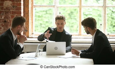 Confident businessman presenting documents to clients,...