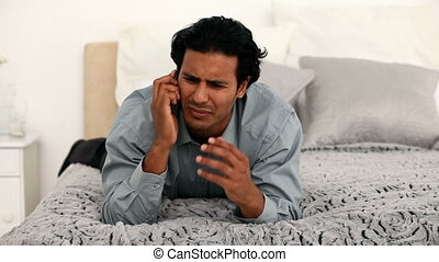 Furious man on the phone on his bed at home