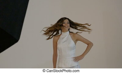 Young woman in a white suit is participating in a photo...