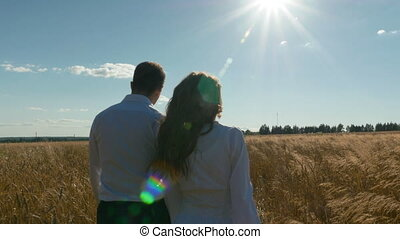 A man and a woman in white suits are walking along the field with wheat. slow motion