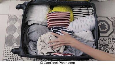 Top view mom packs baby things in suitcase