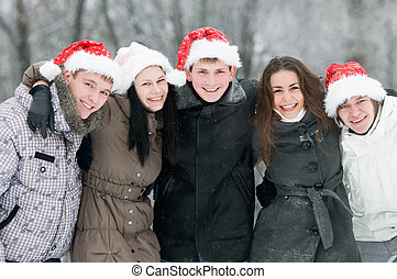 group of smiling young people in winter