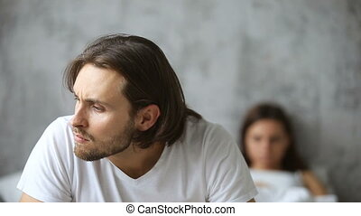 Man upset after quarrel sitting on bed, woman at background...