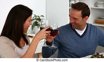 Lovely couple clinking glasses of red wine during lunch