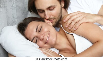 Affectionate husband wakening up sleeping wife by kissing,...