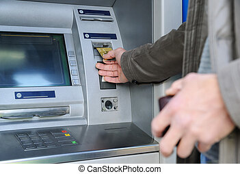 Inserting a bank card. - A man is inserting a bank card into...