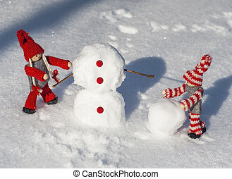 wooden dolls in red knitted clothes roll down snowballs to...