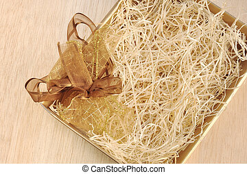 Open gift box and bow - filled with packing bast