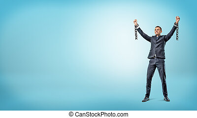 A happy businessman stands with hands raised in victory...