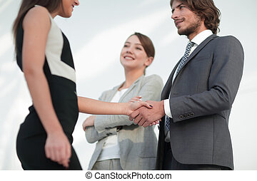 Businesspeople shaking hands against room with large window...
