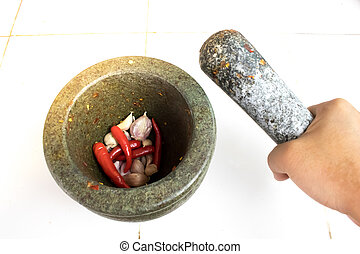 Pestle in woman hand above the mortar with chilli and garlic...