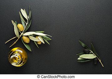 Olive oil and olive branch on black background