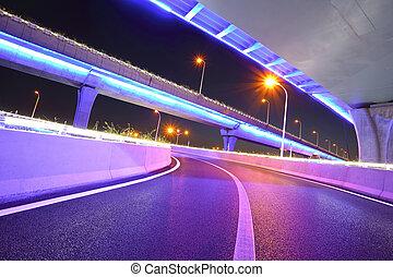 Empty road floor with city viaduct bridge of neon lights...