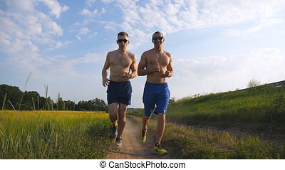 Two muscular men running outdoors. Young athletic guys...
