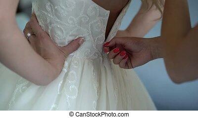 Zipping up bridal dress closeup