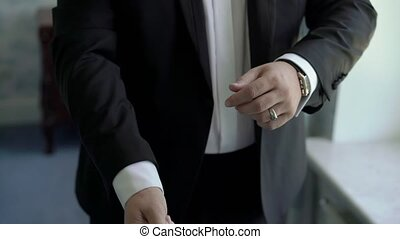 Man buttoning jacket - Man buttoning black jacket closeup