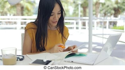 Smiling woman working outside - Young pretty girl writing in...