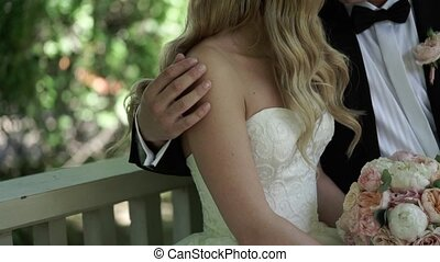 Bride and groom hugging on a bench slow motion