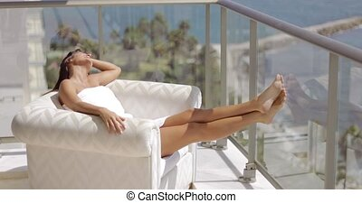 Woman enjoying tropical light on terrace - Young content...