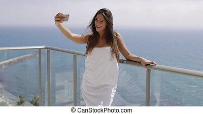 Content girl taking selfie on resort - Young happy woman...