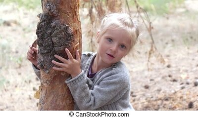 Girl hugging a tree - Girl child listens to a tree with a...