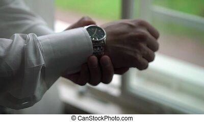 Man put on wrist watches closeup