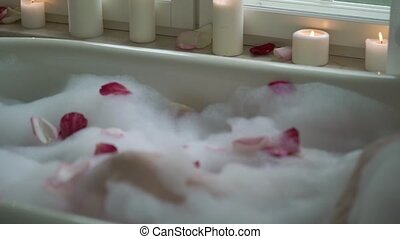 Young woman in bathroom with petals and candles