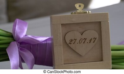 Wedding rings in wooden box and bridal bouquet