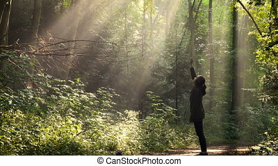 girl standing at the morning forest after the rain