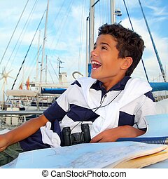 boy teen sailor laying on marina boat chart map smiling in...