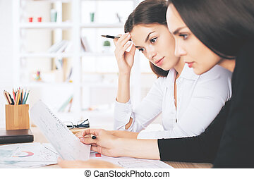 Females doing paperwork - Portrait of two beautiful...