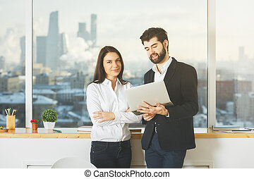White people using laptop - White businessman and woman...
