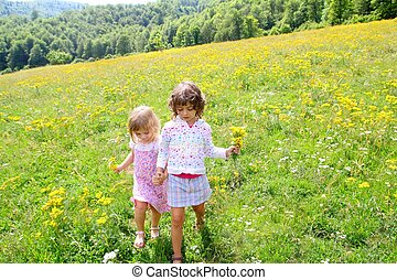 sister girls in meadow playing with spring flowers