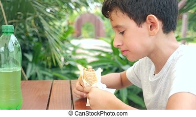 An attractive boy eats a fresh bread pita with a salad of...
