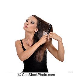 Beautiful young woman brushing her hair hairbrush.