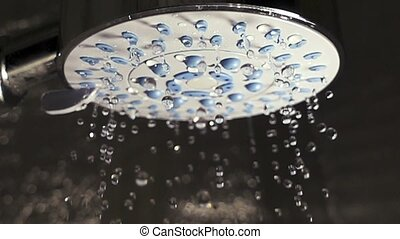 Water drops in the shower head. Slow motion.