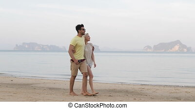Couple Walking On Beach Embracing Talk, Young Man And Woman...