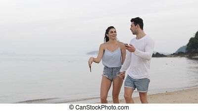 Couple Walking On Beach Holding Cell Smart Phones Talking,...