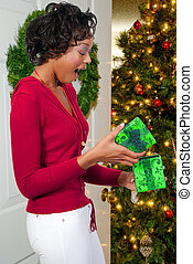 Black Woman Holding a Christmas Ornament - A beautiful young...