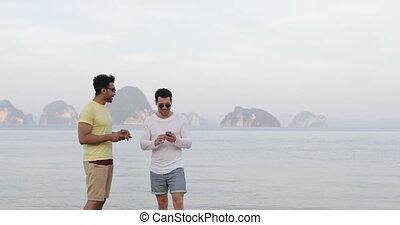 Two Man On Beach Using Cell Smart Phones Talking Gay Couple...