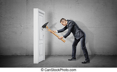 A businessman hits a small white and closed door but his...