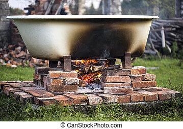 Improvised hot bathtub with fire underneath. - Improvised...
