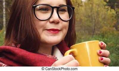 Young woman drinks hot tea from a mug to keep warm
