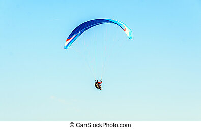 Man paragliding with blue parachute above water sea, clear...