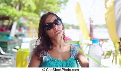 Pretty girl wearing sunglasses drinking water in beach cafe....