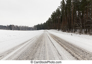 snow-covered road in the winter season. On the side of the...