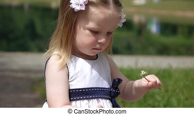 Child with dandelion - Girl baby sniffing dandelion and...