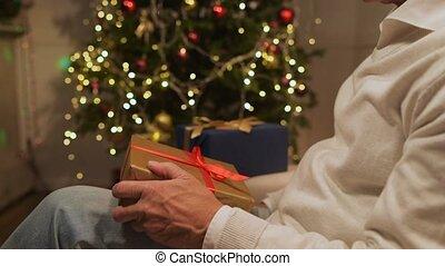 Pleasant senior man preparing Christmas presents - Home...