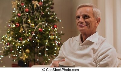 Delighted aged man drinking tea at home - Christmas eve....