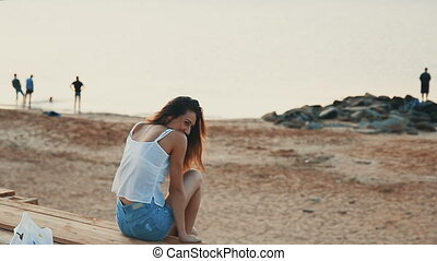 Happy young woman sitting and laughing on the morning beach...